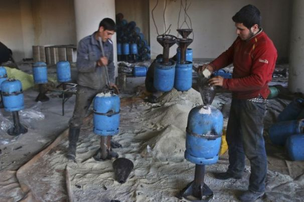"Men fill gas canisters with explosive for usage with a cannon named ""Borkan"" (Volcano) inside a weapon factory in Aleppo countryside March 5, 2015. The ""Borkan"" is made out of four tubes attached to a loader, which can fire four shells at a time, and have a range of three kilometres (1.86 miles).    Picture taken March 5, 2015. REUTERS/Abdalrhman Ismail (SYRIA - Tags: CIVIL UNREST CONFLICT) - RTR4SGAQ"